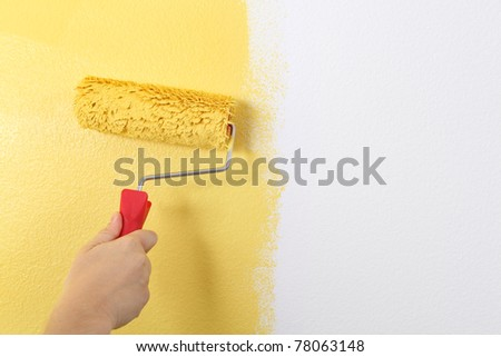 Photo of painting a wall with a roller and yellow paint. - stock photo