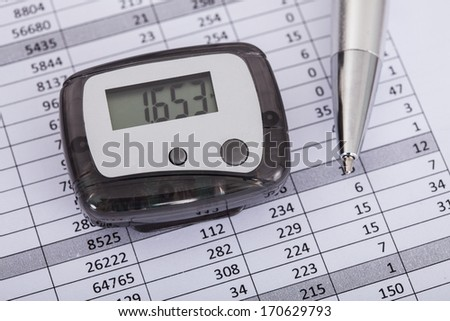 Photo Of Pedometer With Pen Over Document - stock photo