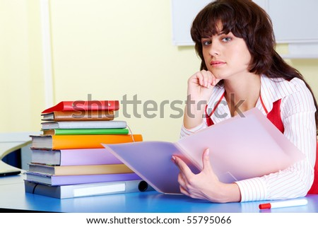 Photo of pensive teacher sitting at the desk and looking at camera - stock photo
