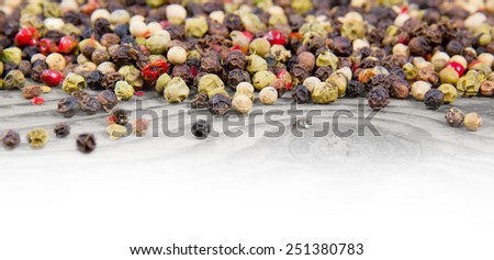 Photo of pepper seeds on wooden board with white space for text - stock photo