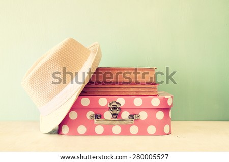 photo of pink suitcase with polka dots, fedora hat and stack of books over wooden table, retro style image  - stock photo