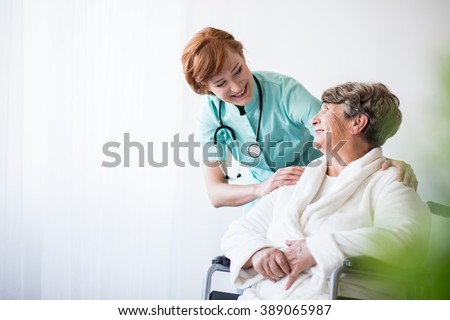 Photo of positive doctor and patient on wheelchair - stock photo