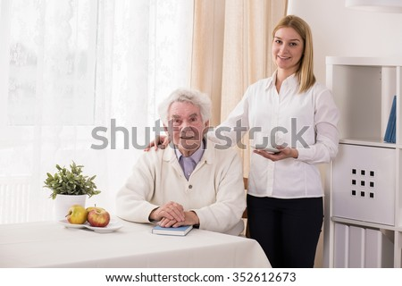 Photo of positive private caregiver and old man - stock photo