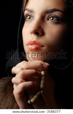 Photo of praying woman in black hood - stock photo