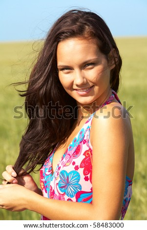 Photo of pretty girl in colorful dress looking at camera on sunny day - stock photo