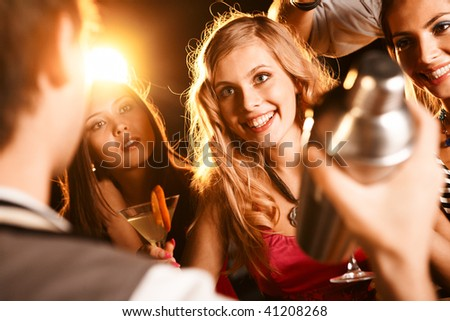 Photo of pretty girl with cocktail looking at barman at party - stock photo