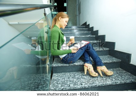 Photo of pretty girl with coffee reading paper on stairs of college - stock photo
