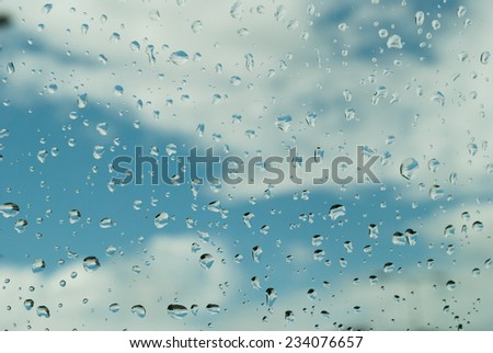 photo of rain drops on glass with cloudy sky on background - stock photo