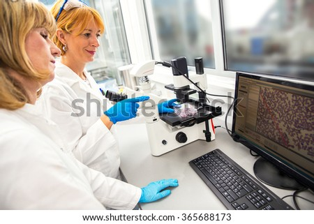 Photo of real female scientists researching in laboratory. - stock photo