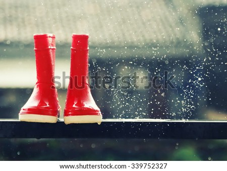 Photo of red boots under rain - stock photo