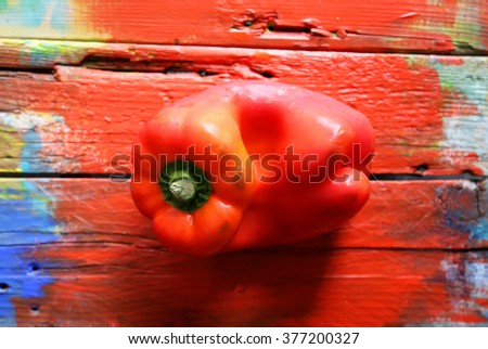 Photo of red pepper on red wooden background - stock photo
