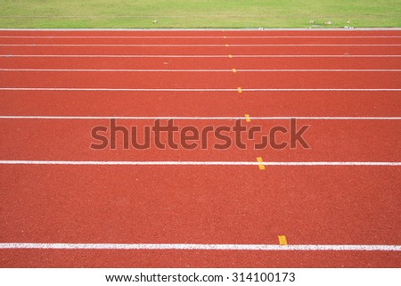 Photo of red running track with green grass - stock photo