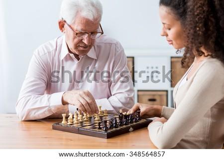 Photo of retiree and caregiver playing chess - stock photo