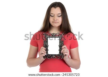 Photo of sad teenage girl with photo frame on white background - stock photo