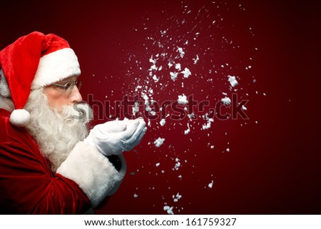 Photo of Santa Claus blowing snow and looking at it - stock photo