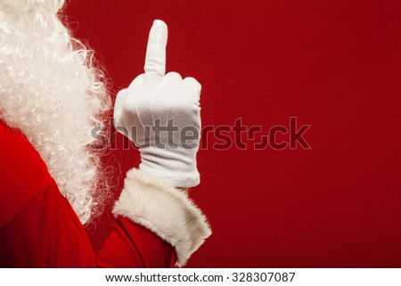 Photo of Santa Claus gloved hand in pointing gesture. fingers. - stock photo