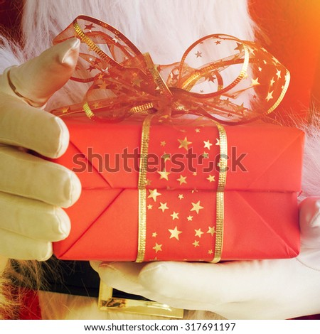 Photo of Santa Claus gloved hands holding giftbox - stock photo