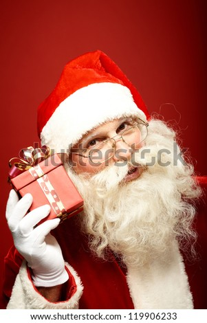 Photo of Santa Claus holding red giftbox by his ear - stock photo