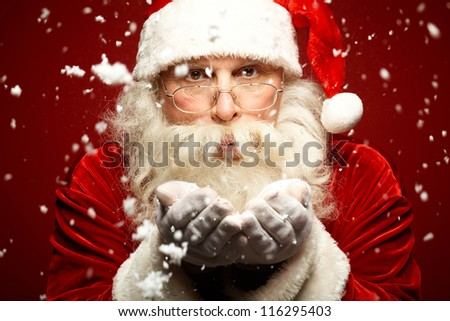 Photo of Santa Claus in eyeglasses blowing snow and looking at camera - stock photo