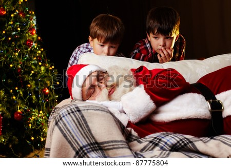 Photo of Santa Claus sleeping on sofa with two amazed kids looking at him - stock photo