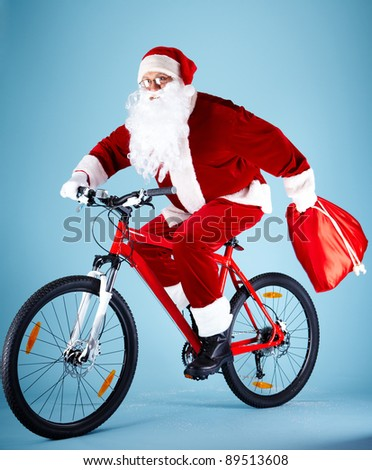 Photo of Santa Claus with red sack riding bike - stock photo