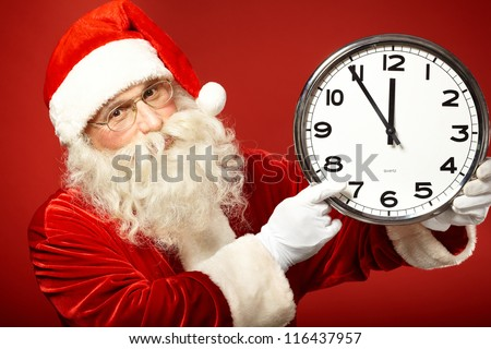 Photo of Santa pointing at clock showing five minutes to midnight - stock photo