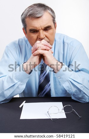 Photo of senior employer thinking about something at workplace - stock photo
