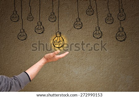 photo of senior man hand and sketch of on and off light bulbs in front of empty textured wall . creativity and solution concept - stock photo