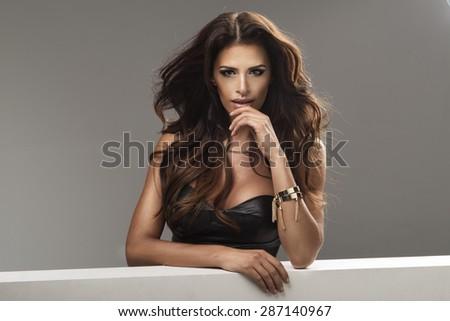 Photo of sensual beautiful woman looking at camera, posing in black  top.  - stock photo