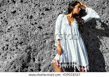 Photo of sensual sexy beautiful young brunette hippie model girl  in white dress posing outdoor near gray wall - stock photo