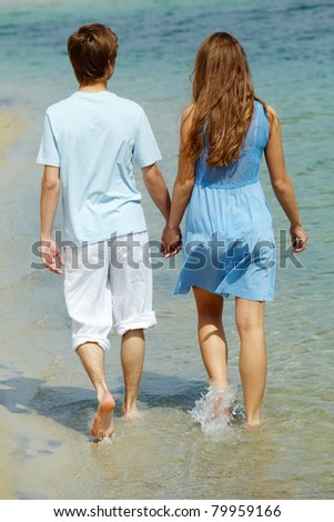 Photo of serene couple walking in water on summer vacation - stock photo