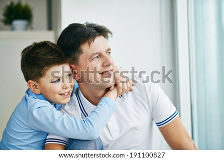 Photo of serene man and his son looking through window - stock photo