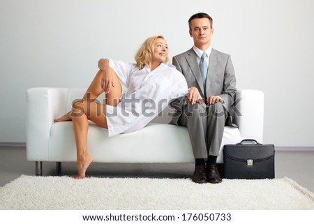 Photo of serious man in suit sitting on sofa with seductive happy woman near by - stock photo