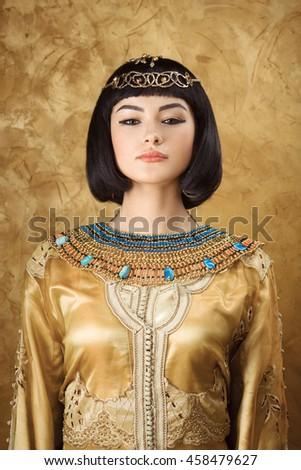 Photo of serious woman with Cleopatra makeup, closeup portrait of beautiful female with stylish haircut agaist golden background, young lady wearing fashionable golden necklace, beauty salon - stock photo
