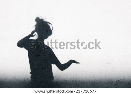 Photo of shadows of young dj woman with headphones mixing music. - stock photo