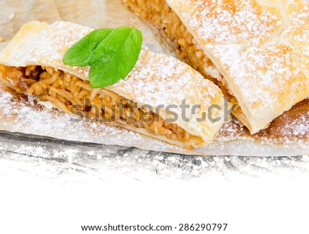 Photo of sliced apple strudel on wooden board with white space - stock photo