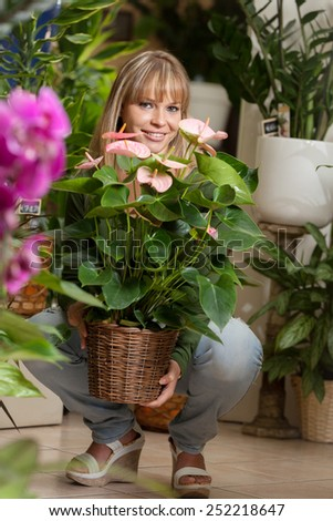 photo of smiling caucasian woman choosing a plant in a flower shop - stock photo