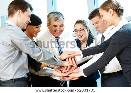 Photo of smiling co-workers making pile of hands and looking at camera - stock photo