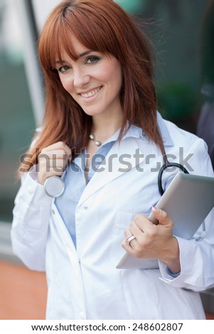 photo of smiling female doctor standing outside with tablet pc - stock photo