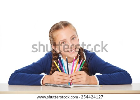 Photo of smiling school girl sitting in school desk and holding colorful pencils. Isolated on white background. Concept for school life - stock photo