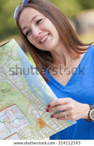 Photo of smiling woman with the map, tourism concept - stock photo