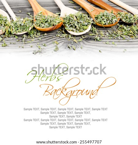 Photo of spoons with dried herb leaves on wooden board, white space for text - stock photo