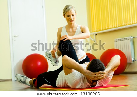 Photo of sportsman doing physical exercise while his pretty instructor helping him in the gym - stock photo