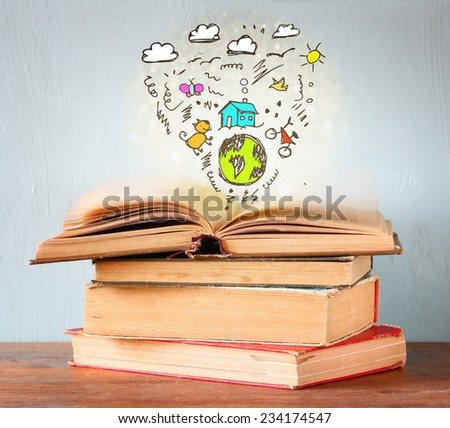 photo of stack of books over wooden table. top book is open with set of infographics icons. create a better world concept or education concept - stock photo