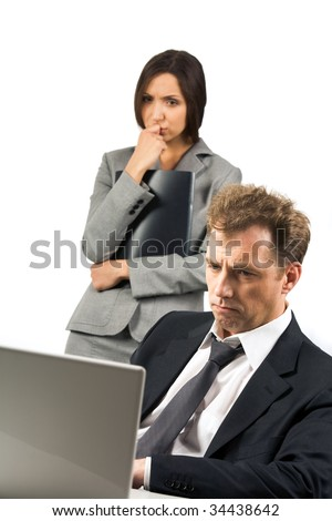 Photo of stressed businessman looking at laptop screen with scared woman at background - stock photo