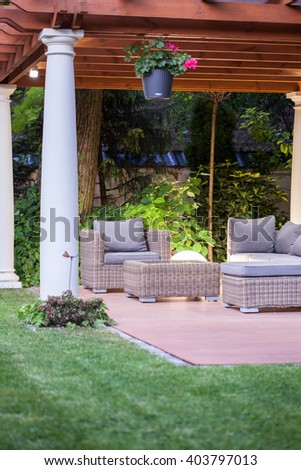 Photo of stylish covered patio with columns in villa garden - stock photo