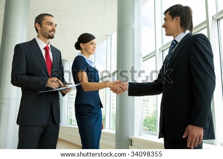 Photo of successful business partners handshaking after striking great deal with smiling man near by - stock photo