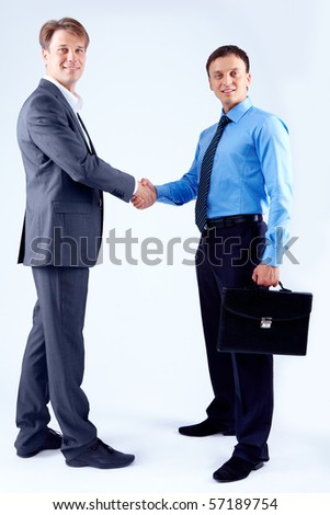 Photo of successful business partners handshaking and looking at camera - stock photo