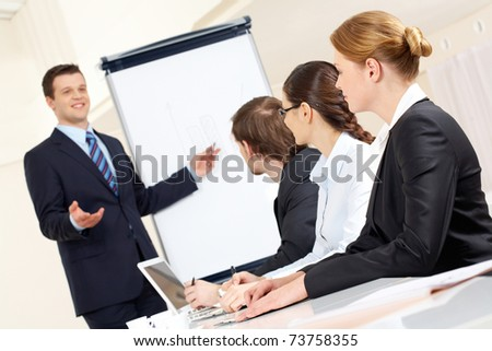 Photo of successful businessman sharing ideas by whiteboard with partners at presentation - stock photo