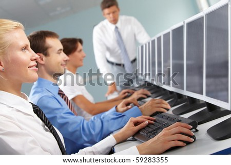 Photo of successful businesspeople typing and looking at monitors in line - stock photo